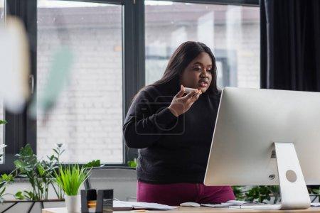 Afrikanische amerikanische Plus-Size-Unternehmerin nimmt Sprachnachricht auf und blickt auf Computermonitor