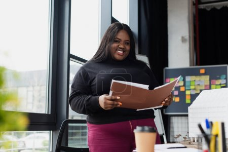 Photo for Smiling african american plus size woman holding folder in office - Royalty Free Image