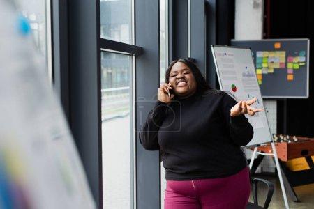 sonriente afroamericano más tamaño mujer hablando en el teléfono inteligente en la oficina