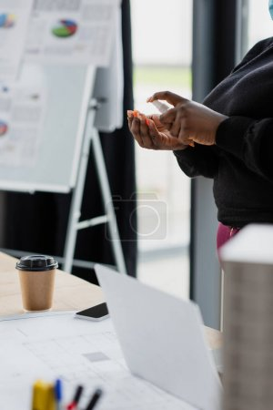 Photo for Cropped view of african american plus size businesswoman applying sanitizer in office - Royalty Free Image
