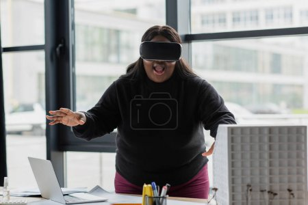 Photo for Amazed african american plus size engineer in vr headset near carton house model - Royalty Free Image