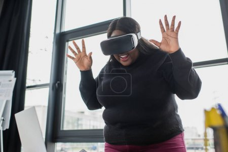 exited african american plus size woman in vr headset gesturing near laptop