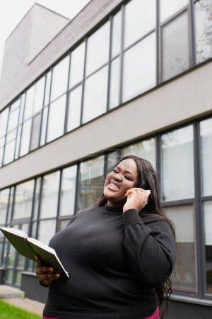 Photo pour Souriant afro-américain plus taille femme tenant un carnet et parlant sur smartphone à l'extérieur - image libre de droit
