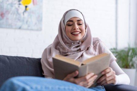 Photo pour Femme musulmane gaie lisant le livre à la maison, premier plan flou - image libre de droit