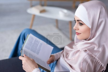 Photo for Dreamy muslim woman looking away while sitting with book at home - Royalty Free Image