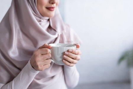 Photo pour Vue recadrée de femme musulmane floue dans le hijab tenant une tasse de thé à la maison - image libre de droit