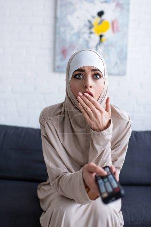 Photo pour Femme musulmane choquée couvrant la bouche avec la main tout en regardant la télévision à la maison - image libre de droit