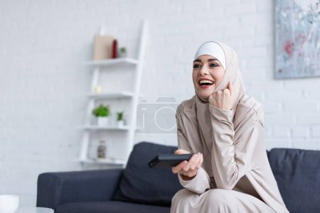 Photo for Excited arabian woman laughing while watching movie at home - Royalty Free Image