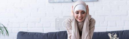 Photo pour Femme musulmane joyeuse touchant la tête tout en souriant à la maison, bannière - image libre de droit