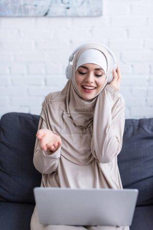 Photo for Joyful muslim woman in headphones pointing at laptop during webinar - Royalty Free Image