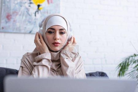Photo pour Jeune femme arabe ajustement casque pendant la leçon en ligne sur ordinateur portable flou - image libre de droit