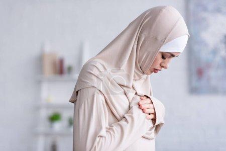 Photo pour Jeune femme musulmane tenant la main sur la poitrine tout en priant les yeux fermés - image libre de droit