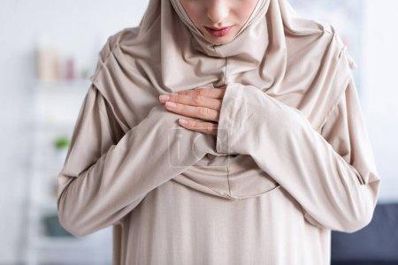 Photo pour Vue partielle de jeune femme musulmane tenant la main sur la poitrine tout en priant à la maison - image libre de droit