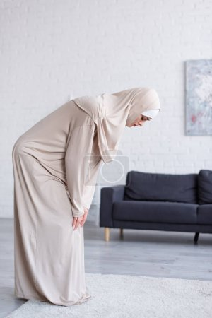 Photo pour Vue latérale de la femme musulmane en vêtements traditionnels priant à la maison - image libre de droit
