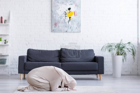 Photo pour Jeune femme musulmane priant sur le sol dans le salon - image libre de droit