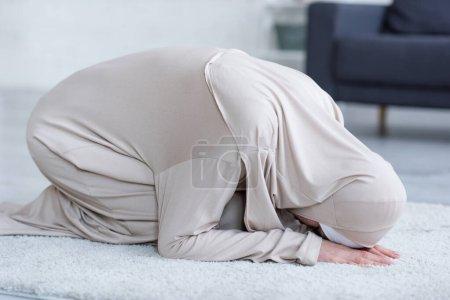 Photo pour Femme musulmane en vêtements traditionnels priant sur le sol à la maison - image libre de droit