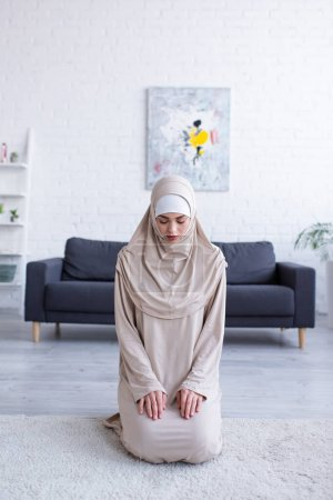 Photo pour Jeune femme musulmane priant tout en étant assis sur le sol avec les yeux fermés - image libre de droit