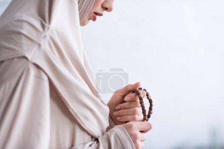 Photo pour Vue partielle de la jeune femme arabe tenant le chapelet pendant la prière à la maison - image libre de droit
