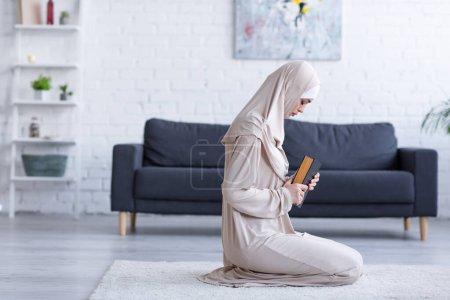 Photo pour Vue latérale de la femme musulmane priant avec le koran sur le sol à la maison - image libre de droit