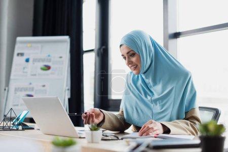 Photo pour Femme d'affaires musulmane souriante pointant vers un ordinateur portable tout en travaillant au bureau, premier plan flou - image libre de droit