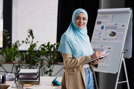 Photo for Happy muslim businesswoman writing in notebook near flip chart on blurred background - Royalty Free Image