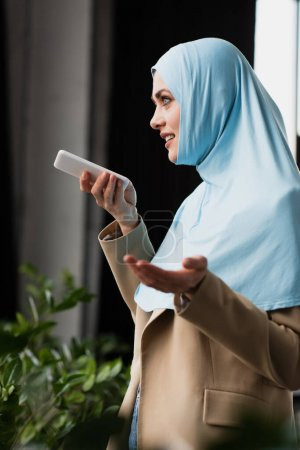 Photo for Pretty muslim businesswoman gesturing while sending voice message on smartphone - Royalty Free Image