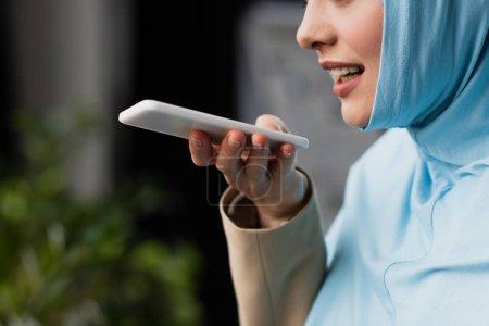 Photo pour Vue partielle de la femme d'affaires musulmane envoyant un message vocal sur son téléphone portable - image libre de droit