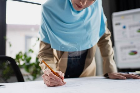 Photo for Cropped view of blurred muslim engineer drawing blueprint in office - Royalty Free Image