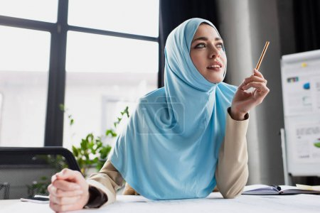 Photo for Positive muslim engineer holding pen while thinking in office - Royalty Free Image