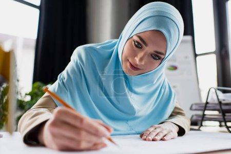 Photo pour Jeune designer musulman dessin au crayon au premier plan flou - image libre de droit