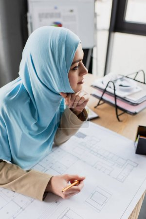 Photo pour Ingénieur musulman réfléchi tenant crayon près du plan directeur dans le bureau - image libre de droit