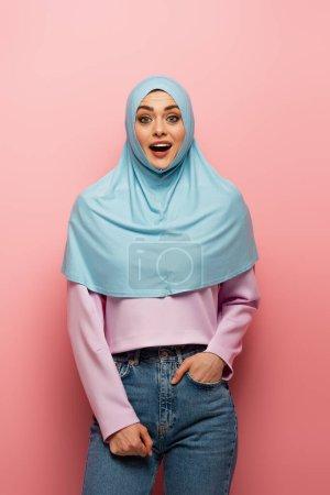 Photo pour Femme musulmane étonnée en jeans debout avec la main dans la poche sur fond rose - image libre de droit