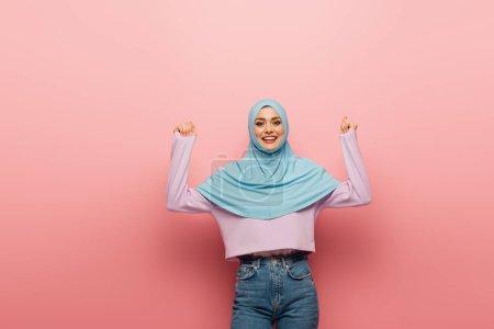 Photo pour Femme musulmane excitée en hijab et jeans montrant geste de joie sur fond rose - image libre de droit