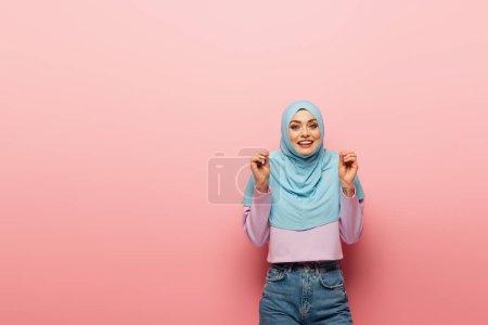 Photo pour Gai et excité femme musulmane geste sur fond rose - image libre de droit