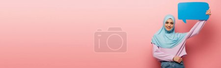 Photo for Cheerful muslim woman with speech bubble looking at camera on pink background, banner - Royalty Free Image