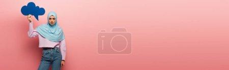 Photo pour Jeune femme musulmane en hijab bleu et jeans tenant bulle de pensée sur fond rose, bannière - image libre de droit