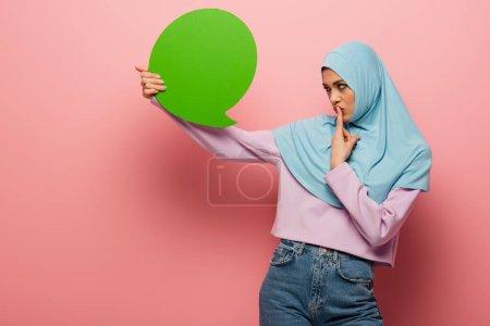 Photo pour Femme musulmane réfléchie toucher les lèvres tout en regardant la bulle de pensée verte sur fond rose - image libre de droit