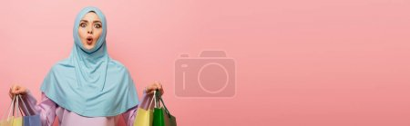 Photo for Thrilled arabian woman in hijab holding purchases isolated on pink, banner - Royalty Free Image