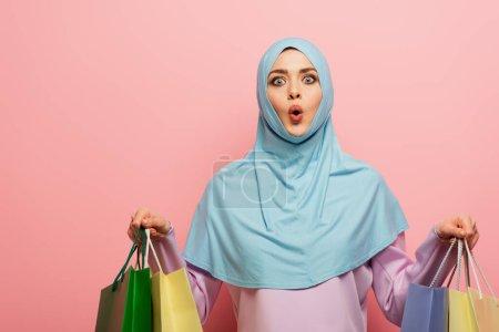 Photo pour Femme musulmane étonnée regardant la caméra tout en tenant des achats sur fond rose - image libre de droit
