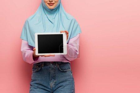 Photo pour Vue partielle de la femme musulmane souriante tenant tablette numérique avec écran blanc sur rose - image libre de droit