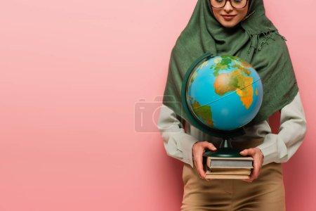 Photo pour Vue recadrée du professeur musulman tenant globe et manuels sur fond rose - image libre de droit