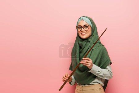 Photo pour Femme musulmane joyeuse avec bâton de pointage souriant à la caméra isolée sur rose - image libre de droit