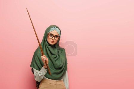 Photo pour Jeune professeur d'arabe en hijab vert tenant bâton de pointage isolé sur rose - image libre de droit