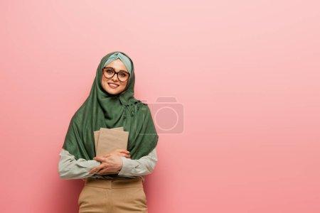 Photo pour Jolie prof musulmane avec des manuels souriant à la caméra sur fond rose - image libre de droit