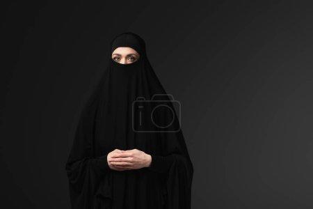 Photo pour Arabe femme en noir niqab et amaya regarder caméra isolé sur noir - image libre de droit