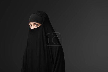 Photo pour Jeune femme musulmane en noir vêtements traditionnels regardant caméra isolé sur noir - image libre de droit