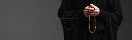 Photo pour Vue recadrée de religieuse musulmane avec chapelet priant isolé sur gris foncé, bannière - image libre de droit
