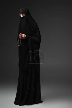 Photo for Full length view of muslim woman in black niqab praying with rosary on dark grey background - Royalty Free Image