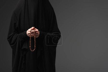 Photo pour Vue partielle de la religieuse musulmane en abaya noir tenant des perles de prière isolées sur gris foncé - image libre de droit