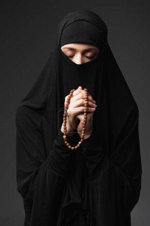 Photo pour Jeune femme musulmane avec les yeux fermés tenant chapelet tout en priant isolé sur noir - image libre de droit
